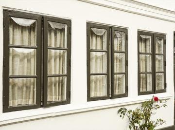 Nymalet hvid husfacade og mørkegrønne vindueskamme i klassisk look