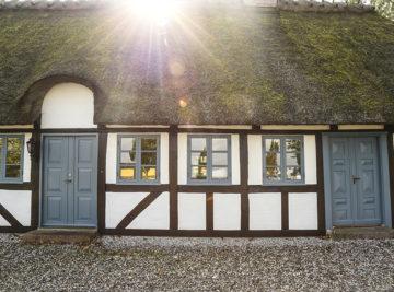 Nymalet bindingsværkshus i klassisk hvid og sort med blålige vinduer og døre