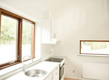 Nymalet hvidt køkken og olierede vindueskamme